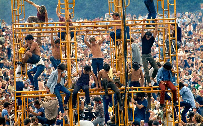 Bethel, New York, August 1969. The crowd and people sitting on the sound tower. (Courtesy of Elliott Landy/The Image Works)