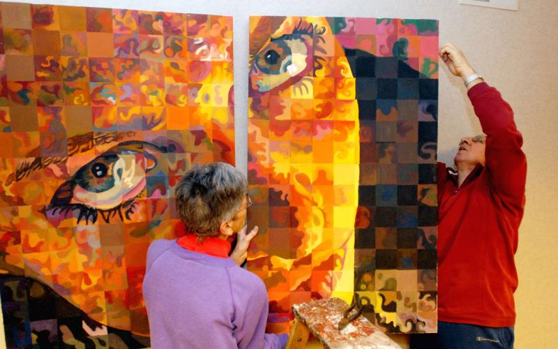 <P>Dee Valvano (left) and her husband Vince hang artwork for a Feb. 8-10 show at St. Mary Parish in Canandaigua. <I>