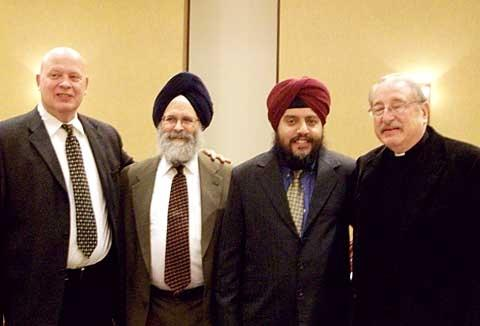 Deacon John Brasley (from left), Ralph Singh, Chetan Singh Rakieten and Father Norman Tanck pose for a photo during a Nov. 18 meeting of members of the Sikh and Catholic communities at the diocesan Pastoral Center in Gates.