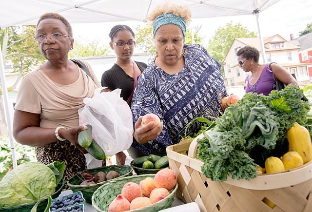 Joann Vauss (from left), Sarah Ash and Stella Ash shop for fresh produce at the farm stand outside of T&K Fresh Corner store on Carter Street in Rochester Aug. 8.