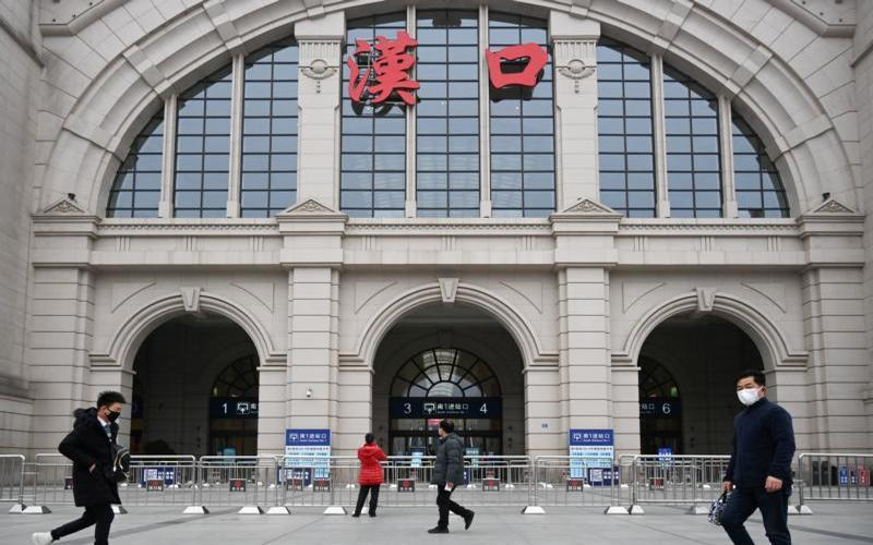 People walk past the closed Hankou Railway Station