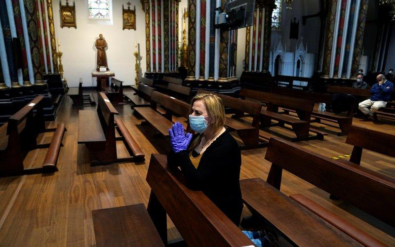 A woman wearing protective gloves and a mask praying in a nearly empty church