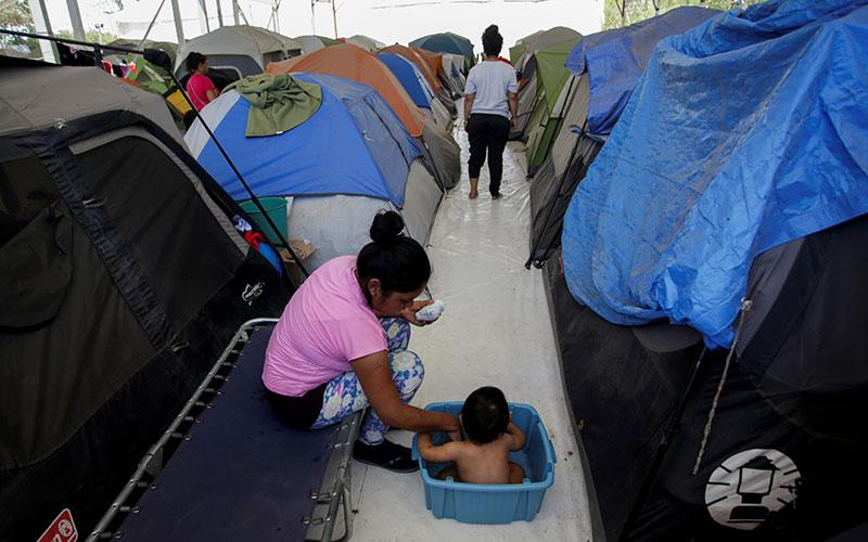 A migrant woman bathes her son outside their tent at a migrant encampment in Matamoros, Mexico, April 30, 2020, where more than 2,000 people live while seeking asylum in the U.S, as the spread of the coronavirus continues.