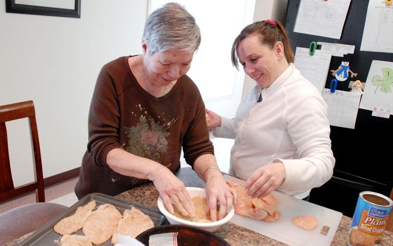 Catholic Charities Community Services recently opened Crowley House, a home for the developmentally disabled in Lyons. Above, Crowley House resident Alice Rogers (left) helps resident-support specialist Michelle Lewis prepare dinner March 12.