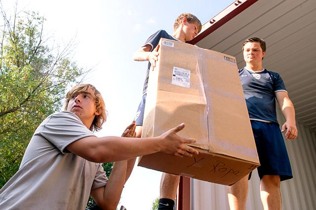 On Aug. 20, parishioners of St. Francis-St. Clare Parish and members of the Seneca Falls and Waterloo communities pitched in to load a tractor-trailer truck with boxes of donated items that had been collected for needy people in Nicaragua. Above, Ben McDonald (from left) passes a box of donated goods to Jeremy Porter and Nick Hartwell to place in the truck.