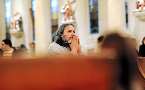 Deacon Jorge Malave prays during an April 2009 reconciliation service at Our Lady of Perpetual Help Church in Rochester.