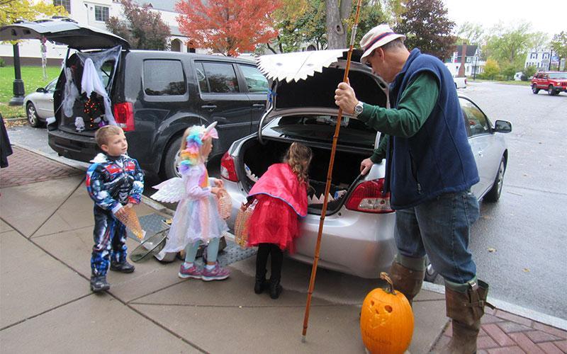 Kindergarten and Preschool students Tyler Hanvey, Harper Harrigan and Andrea Powell-Warner retrieve treats from  Mark Figura's shark car at St. Agnes School's Trick or Trunk event on Halloween.