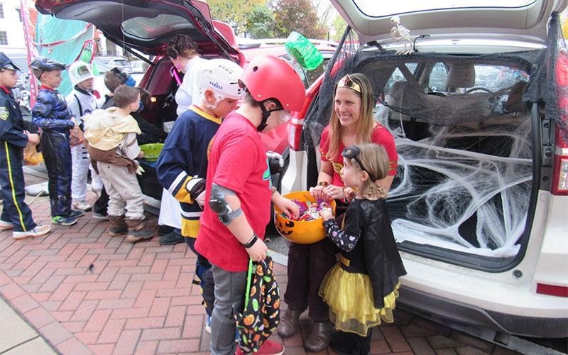 Preschool student Mary Alice Schlueter helps her mom Rachael Schluter hand out candy at this year's Trick or Trunk event at St. Agnes School