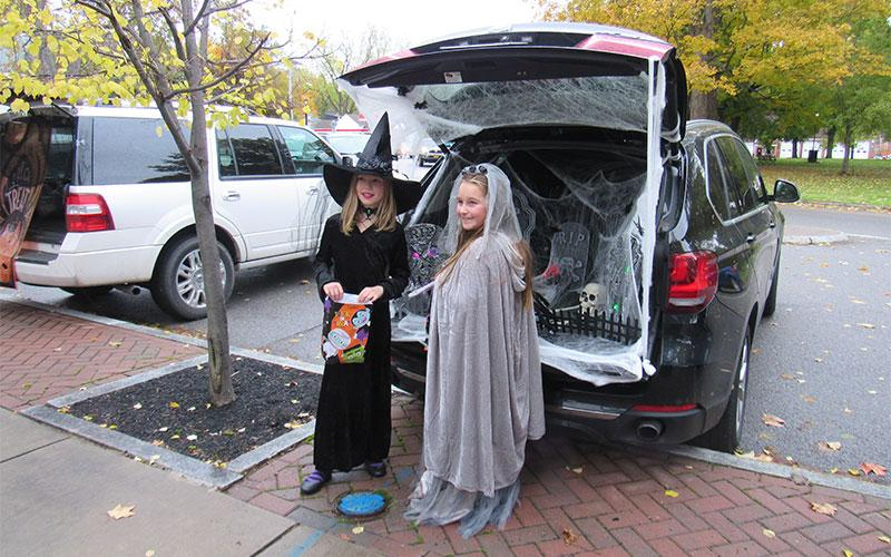 Lydia Kashorek and Hailey Harper by a Graveyard decorated car.