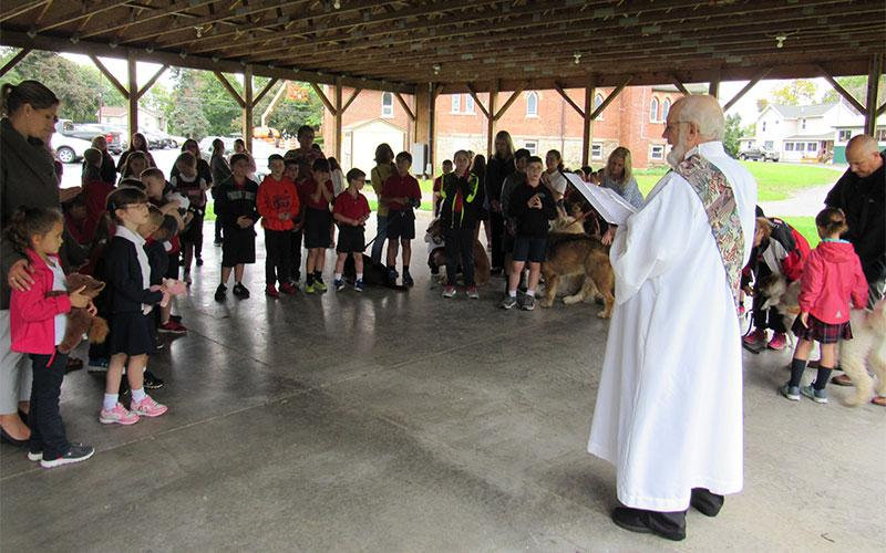 Deacon Greg Emerton says a prayer at the Annual Pet Blessing at St. Agnes School.