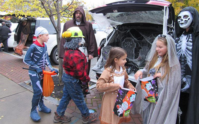 Sawyer Damon, JP Corcoran, Kate Schwan and Hailey Harper get some treats from Randy Harper and Christine Wells Harper at St. Agnes School's Trick or Trunk event.