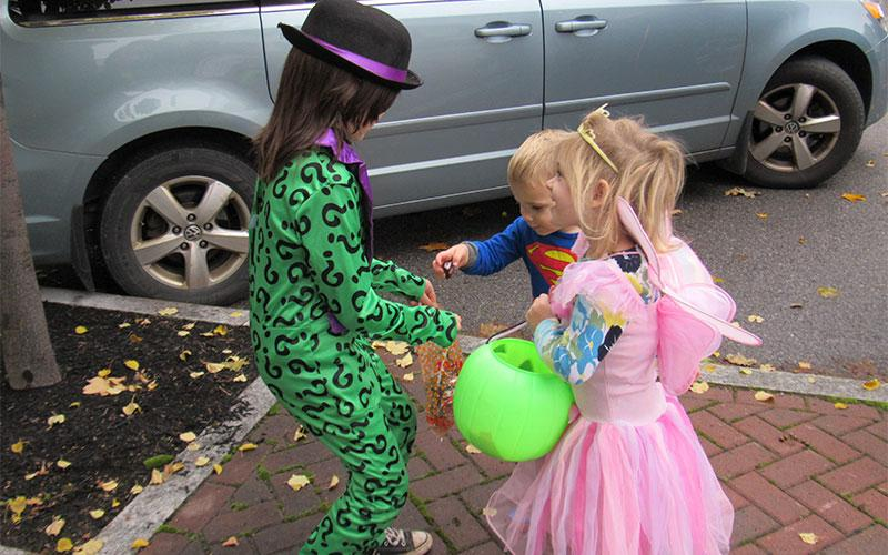 Isaac Yaddaw receives treats from PreSchooler Adelaide Barrett and her brother Charles as they helped at St. Agnes School's Trick or Trunk event