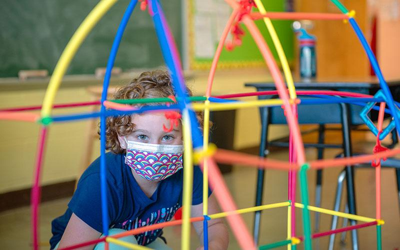 Second-grader Emily Layton wears a mask while playing in a classroom during the All Saint's Academy summer program in Corning July 15.