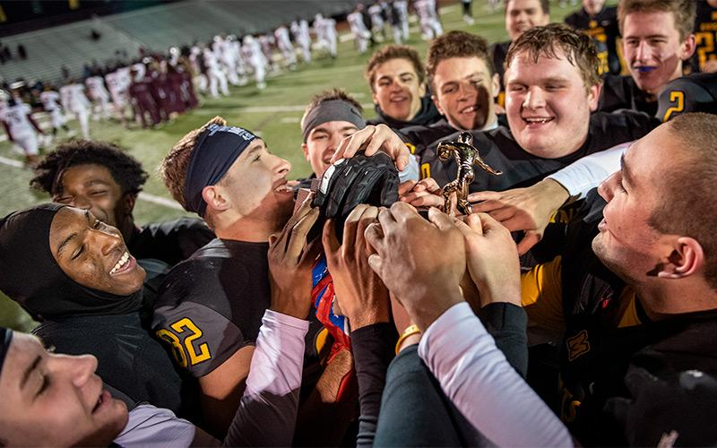 McQuaid Jesuit football players reach forward to touch the Section 5 Class AA trophy following their 30-27 win against Aquinas Institute Nov. 9.