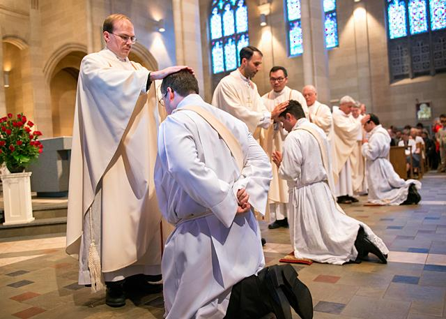 Diocesan priests line up to lay their hands on the heads of newly ordained priests during a June 3 priest ordination Mass at Rochester's Sacred Heart Cathedral.
