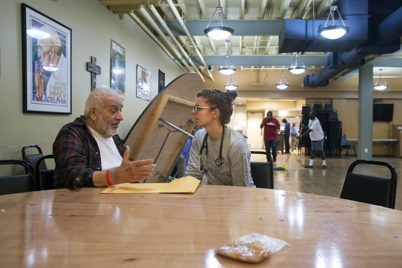 Kelly Sherman talks about his medical history with University of Rochester medical student Emily Norkett Sept. 27 at the House of Mercy, a homeless shelter in Rochester.