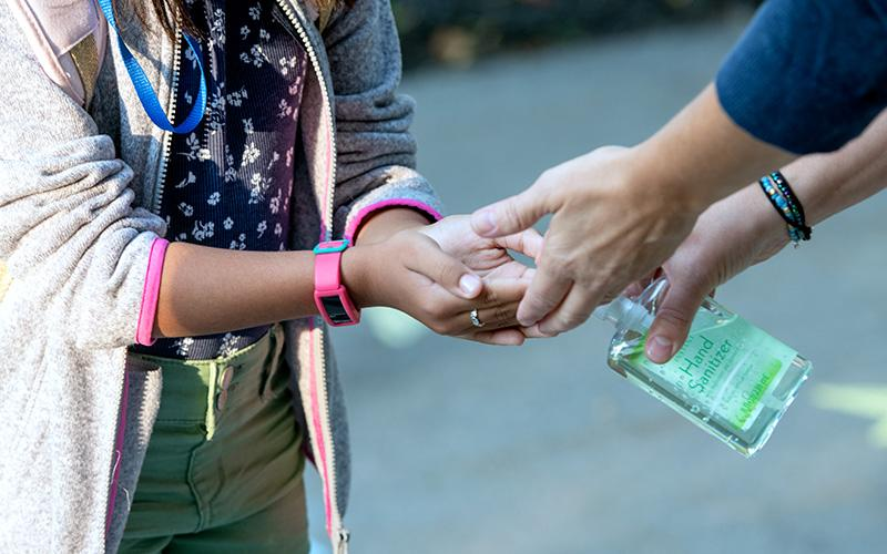 A Seton Catholic School student receives a squirt of hand sanitizer upon arriving at the Brighton school Sept. 9. New York state is now requiring Seton and eight other Catholic schools in Monroe County to test 20 percent of their students, staff and teachers for COVID-19 each week.