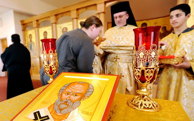 Parishioners of Gates' St. Nicholas the Wonderworker Church stand near an icon of St. Nicholas Nov. 8 as they venerate a cross held by Father Kenneth Sherman. (Courier photo by Mike Crupi)