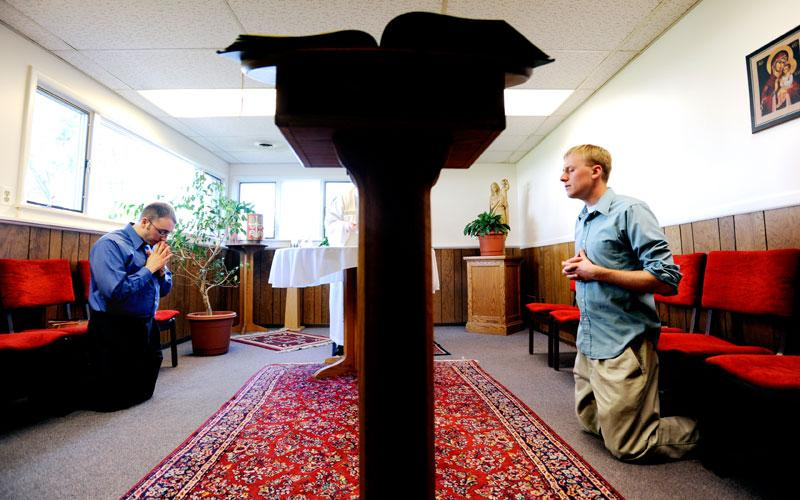 Greg Rupik (left) and Peter Van Lieshout kneel during an April 27 Mass at Becket Hall, thediocesan residence for young men discerning vocations to the priesthood. (Courier photo by Mike Crupi)