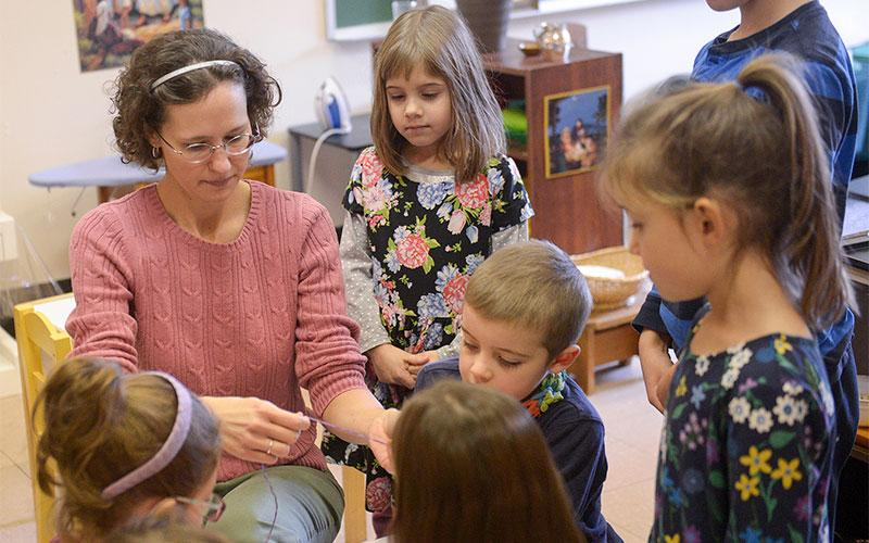 Jen Brannin shows students how to use a needle and thread to sew during the Dec. 18 Catechesis of the Good Shepherd class at Church of the Holy Spirit in Webster. (Courier photo by John Haeger)