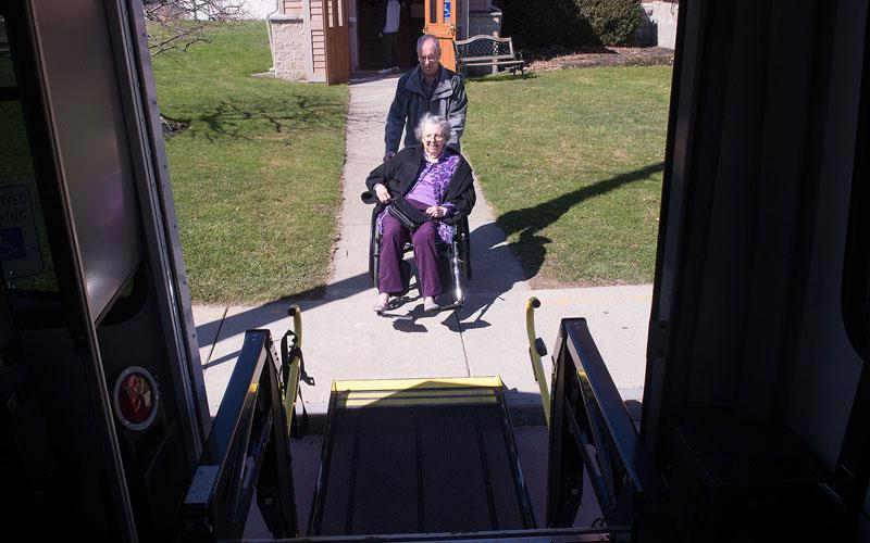 Fred Proietti helps Helen Stewart onto the Sunday Bus following Mass at St. Michael Church in Penn Yan April 22.