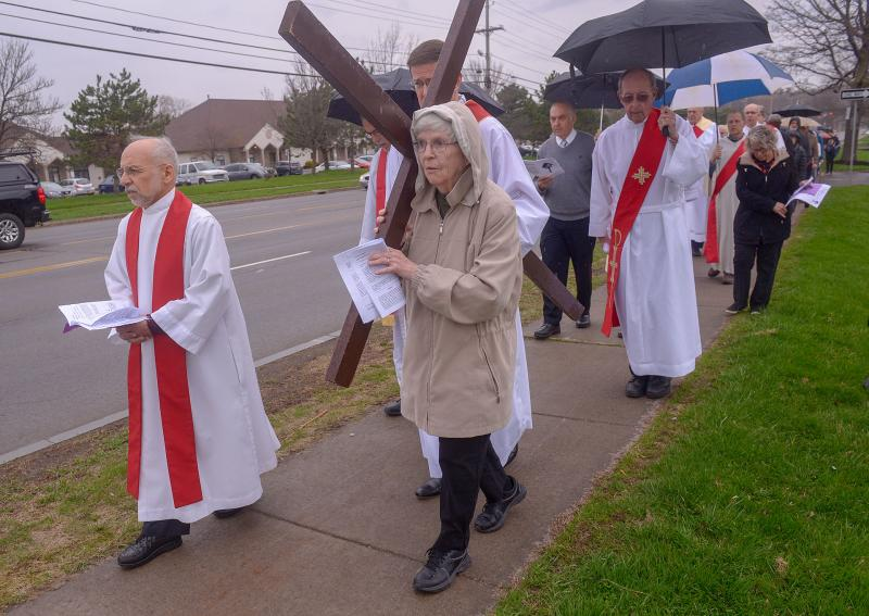 Sister of St. Joseph Ann Urquhart carries a wooden cross as the procession moves toward the third station of the Stations of the Cross in Reparation for Abortion. (Courier photo by John Haeger)
