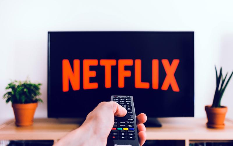netflix on tv with hand on remote