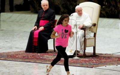 Clelia Manfellotti, a 10-year-old girl with autism from Naples, Italy, runs on stage as Pope Francis leads his general audience in Paul VI hall at the Vatican Aug. 21, 2019.