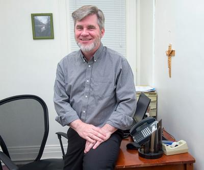 Deacon Gregory Kiley poses in his office at Catholic Charities of the Finger Lakes in Geneva April 26.