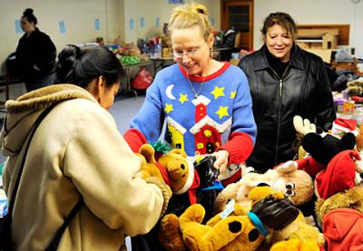 Catholic Charities of Livingston County volunteer Tina Ashley (center) helps Elizabeth Medina (left) and Gena Thomspon pick out children's toys at United Church of Mount Morris Dec. 12 as part of CCLC's Christmas giving program.