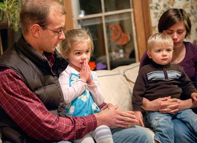 Members of the Walczak family sit on their couch for an evening prayer in this Nov. 2014 file photo.