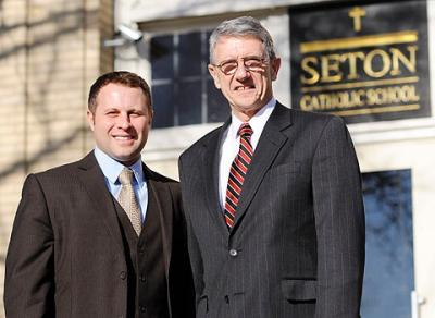 Incoming principal Anthony Cook (left) and outgoing principal Martin Swenson stand outside Seton Catholic School in Brighton Jan. 18.