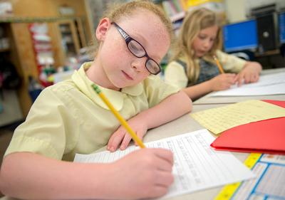 Leah Batterson (left), a second-grader at St. Mary School in Canandaigua, works on a writing assignment in Suzanne Pohorence's class June 12. Pohorence was among 32 teachers helping to create a new curriculum for the Diocese of Rochester's Catholic schools.