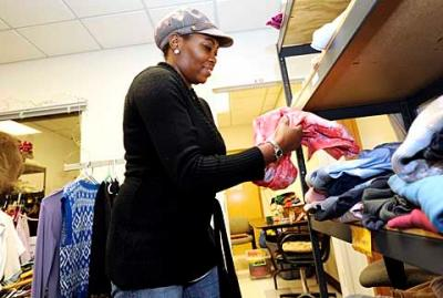 In November volunteer Tracy Williams works in the clothing closet at Catholic Family Center's Community Resource Services branch in Rochester. CFC is a recipient of Catholic Courier/Catholic Charities Christmas Appeal funds.
