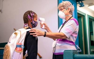 <p>Aleeah Ross has her temperature checked by school nurse Sister Marlene Pape before entering Nazareth Elementary School Sept. 10. (Courier file photo)  </p>