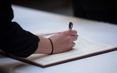 <p>A woman signs her name in the book of enrollment during the 2020 Rite of Election and Call to Continuing Conversion ceremony at St. Mary Our Mother Church in Horseheads. (Courier file photo)  </p>