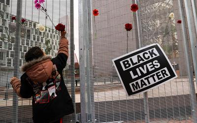 <p>A child in Minneapolis places a flower on a fence near a &ldquo;Black Lives Matter&rdquo; placard during a rally March 7, 2021, the day before jury selection began in the trial of former Minneapolis police officer Derek Chauvin, who is accused of killing George Floyd. (CNS photo by Leah Millis/Reuters)  </p>