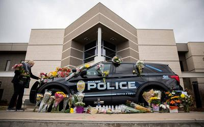 <p>Veronica Hebert of Boulder, Colo., places flowers on the car of Officer Eric Talley March 23, 2021, who was killed the previous day during a mass shooting at the King Soopers grocery store. (CNS photo by Alyson McClaran/Reuters)  </p>