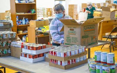 Volunteer Karen Petzke fills an order at Elmira&rsquo;s Most Holy Name of Jesus food pantry March 30.  </p>