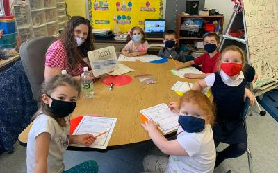 <p>Natalie Heinsbergen, kindergarten teacher at St. Lawrence School in Greece, poses with a group of her students. Heinsbergen is a recent recipient of the Golden Apple Award. (Photo courtesy of St. Lawrence School)  </p>