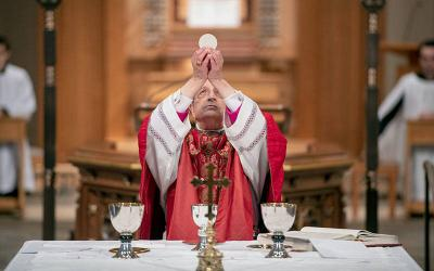 <p>Bishop Salvatore R. Matano elevates the Eucharist during the April 5, 2020, Palm Sunday Mass livestream at Rochester's Sacred Heart Cathedral. (File photo)