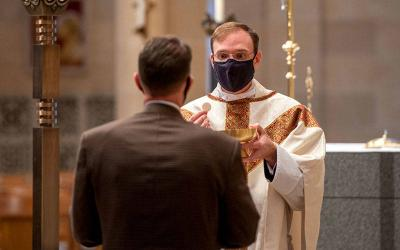 <p>Father Daniel White distributes Communion during an Oct. 19, 2020, Mass at Rochester's Sacred Heart Cathedral.  </p>