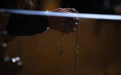 <p>A woman recites the luminous mysteries of the rosary at the Basilica of the National Shrine of the Immaculate Conception in Washington in January. (CNS photo by Tyler Orsburn)  </p>