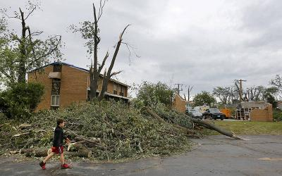 <p>A boy in Woodridge, Ill., walks past damage June 23, 2021, that was left by a category EF-3 tornado. The twister touched down near the parish rectory at St. Scholastica Church in Woodbridge and demolished the garage June 20. A category EF-3 tornado can bring wind gusts of up to 165 mph. (CNS photo by Karen Callaway/Chicago Catholic)  </p>