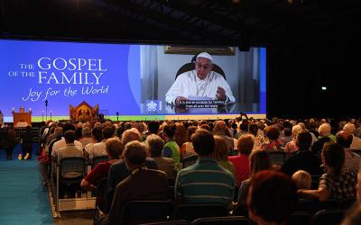 <p>Attendees watch Pope Francis on a screen during the opening ceremony of the World Meeting of Families in Dublin Aug. 21, 2018. (CNS photo by John McElroy, courtesy World Meeting of Families)  </p>