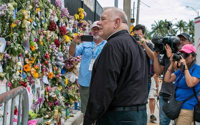 <p>Archbishop Thomas G. Wenski of Miami looks at the Surfside, Fla., Wall of Hope Memorial July 2, 2021, which has risen to remember those missing in the partially collapsed Champlain Towers South. (CNS photo by Ana Rodriguez-Soto/Florida Catholic)  </p>