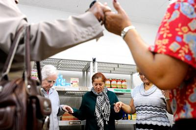 Volunteers pray at the St. Regis Food Cupboard, a ministry of St. Frances Xavier Cabrini Parish, in this 2011 file photo. Several SFXC ministries will receive a $600 stipend from the Catholic Courier/Catholic Charities Christmas Appeal.