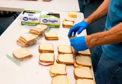<p>Mike Kukiela makes sandwiches Sept. 19 for Holy Family Parish's Lunches with Love program at the former Holy Family School in Auburn.  </p>