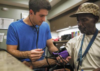 <p>University of Rochester student Stephen Hassig takes the blood pressure of Hubert Wilkenson, a security member at the House of Mercy.   </p>