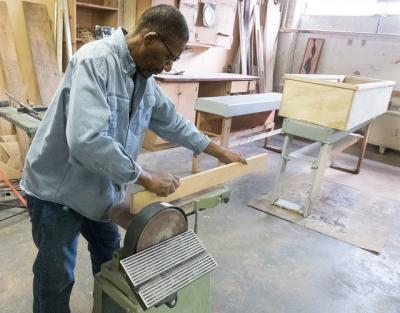 <p>St. Joseph's House of Hospitality volunteer Richmond Futch uses a belt sander to finish a board for a casket he was making Oct. 24. (Courier photo by John Haeger) </p>